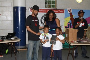 Randy Fisher with 2 kids from Eastchester Community Center in the Bronx holding up the books they won.  There were also 3 winners to the 50 Cent Concert. Also pictured is Keimisa Larrier, Director of the Center, and Charles Fisher.