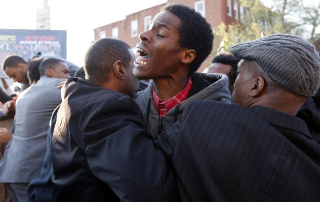 An angry, frustrated citizen is restrained during a Freddie Gray protest. (Courtesy: CNN)