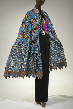 Ensemble; cape in blue & brown hand cut cotton & silk lace; multi-colored polka dot & stripe blouse in silk charmeuse; black crepe pants in wool & silk