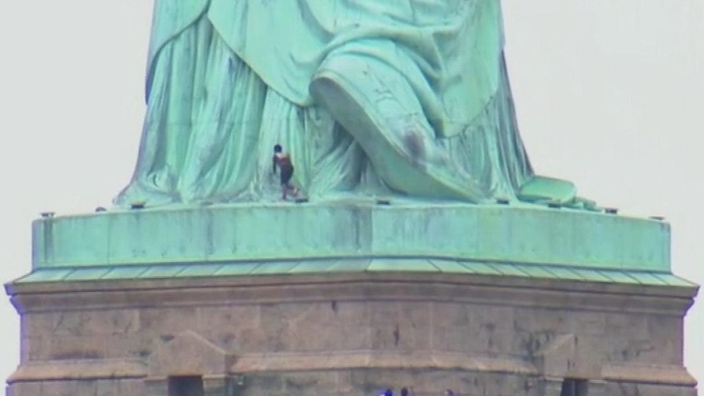 statue of liberty evacuated as woman climbs monument base